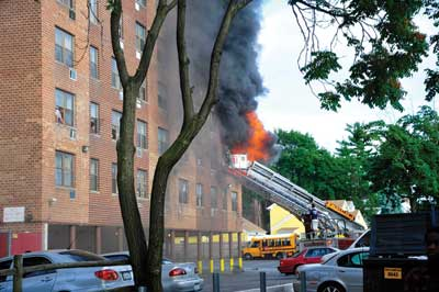 (1) The firefighters in the basket of the tower ladder vent windows of an adjoining apartment.