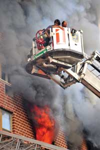 (3) Two civilians are removed from the building with the tower ladder basket.