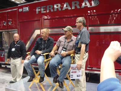 (23) Television personalities Troy and Jacob Landry at the Ferrara booth autographing memorabilia for firefighters.