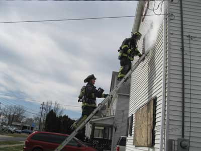 (2) The VES firefighter at the top of the ladder prepares to ventilate the window. The oriented firefighter below him is carrying the thermal imaging camera (TIC).