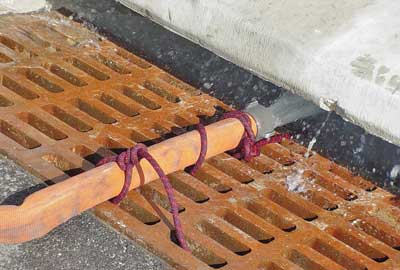 (12) A hose lashed to a storm sewer grating flows water to keep the pump cool.