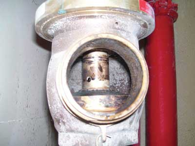 (13) A look inside a hose outlet: Note that the valve's floating stem has no threads, and observe the hole in the valve's stem, which is an inlet for the stem's waterway.