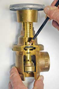 (19) The valve's hand wheel and threaded stem indicate that the valve is open, but it is actually closed because there is no water flowing. Water pressure downstream of the valve, represented by the pencil, exerts a downward force on the piston, closing the floating valve. This photo explains why PRVs cannot be back fed as inlets if an FDC fails.