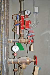 (2) A combination standpipe/sprinkler system. A pressure-reducing sprinkler floor control valve is tapped into the standpipe riser above a pressure-reducing 2½-inch hose outlet. Note the supervisory switch on the floor valve's hand wheel, the water flow switch, and the system side pressure gauge. The pressure-reducing floor valve keeps pressure in the sprinkler piping and heads from exceeding 165 psi. To further safeguard the system, a relief valve, located opposite the system pressure gauge, is set to open at 175 psi and dump water into drain piping, seen to the right of the riser.
