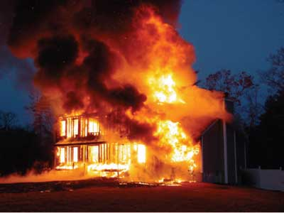 (4) Large, uninterrupted void spaces in modular homes can allow rapid fire spread, as in this fire. In just a few minutes, this occupied structure was fully involved; occupants narrowly escaped and were unharmed. [Photo courtesy of Acushnet (MA) Fire Department.]