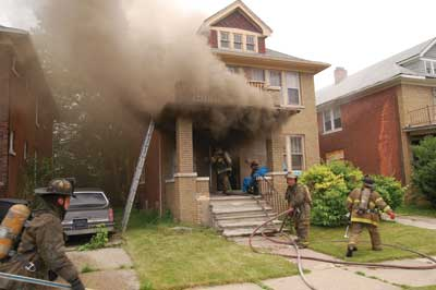 (3) The initial ventilation point at this private-dwelling fire is the front door, which is rarely calculated into the number of ventilation openings that, collectively, impact ventilation-limited fires' tenability. Although the likely location of the fire is the first floor, always check the basement prior to operating above. The presence of board-ups on the basement windows emphasizes this point, as they often conceal fire and smoke conditions. (Photo by Dennis Walus.)