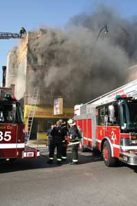 (4) Many cities' truck companies have a roof firefighter position. The roof position allows the IC to get a topside view of the entire fire building through radio reports and can locate any fire showing in the rear and closed shafts much faster than interior companies can. Moreover, this position is able to control ventilation of the interior stairs through the bulkhead door by coordinating this operation with the IC to prevent untenable conditions for those searching for fire inside. (Photo by Tim Olk.)