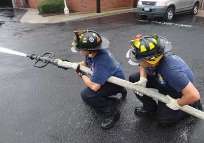 (3) Firefighters demonstrate the proper technique for handling a 2½-inch handline