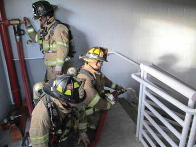 nozzle is flowed on the stair landing below the fire floor