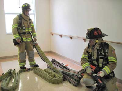 100-foot flat load and two 50-foot Denver loads are deployed on the floor below the fire
