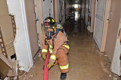third firefighter on the nozzle team, positioned between the attack stairwell and the nozzle