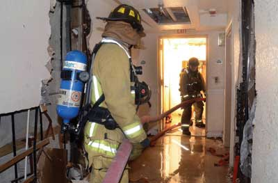 Two mules pull the hose laid out on the floor below the fire and push it up the stairs