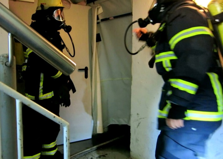 Firefighters in the stairway outside the fire compartment.