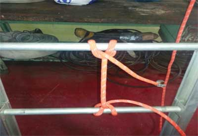 (2-3) Pretie the halyard of the extension ladders toward the end of the extension rope. Fully extend the ground ladder, and tie the rope to a rung. Retract the ladder until it is within the bed. All that will be needed is to pull the rope to extend the fly sections. There is no need to tie or untie. This makes the device more expedient.