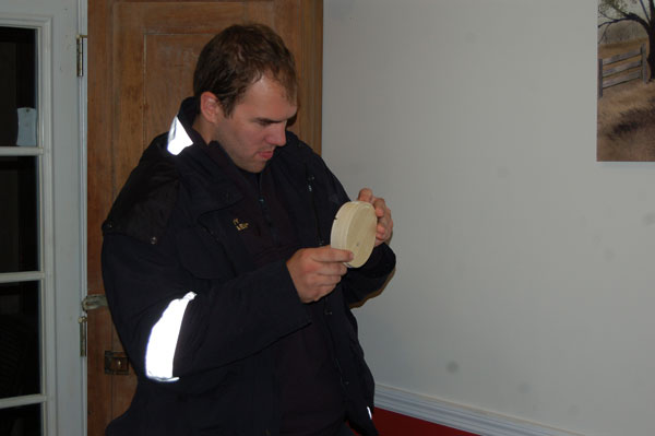 A firefighter examines a smoke alarm.