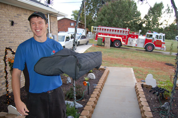 A firefighter makes a home pizza delivery during Fire Prevention Week 2014.