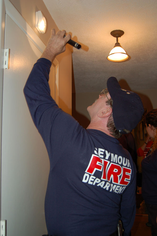 A Seymour firefighter examines a resident's smoke alarm setup.