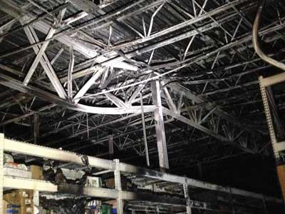 (5-6) One of the girder trusses distorted by the extremely high heat release fire.