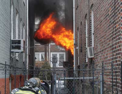 (1) The fire is in the two-story ordinary construction structure. The fire is self-venting out of the first-floor window. The firefighter is getting ready to take the front gate to access the rear yard Allen Epstein