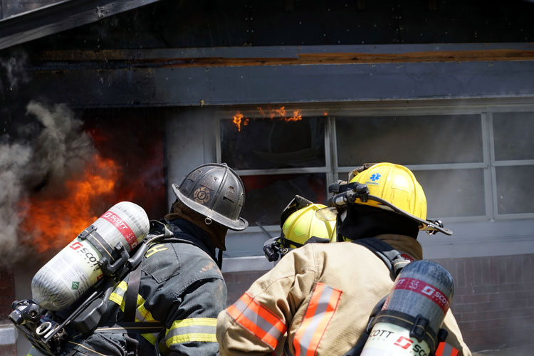 Firefighters confront flames at a burning home
