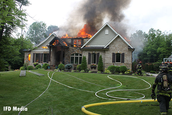 Fire vents through the roof of a residential structure.