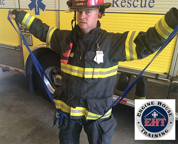 A firefighter demonstrates establishing a hasty harness using webbing.