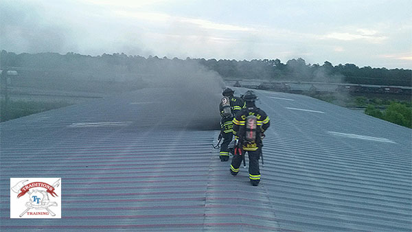 Firefighters operate on the roof of a large building, and smoke wafts up through an opening.
