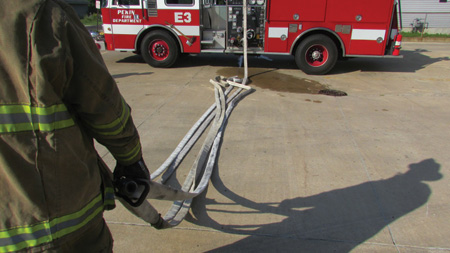 As long as the firefighter maintains the grasps on the loops and nozzle, the hose will stretch cleanly from the pile as the firefighter advances from the apparatus.