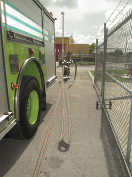 The nozzle firefighter stretches toward the point of entry (the rear of the apparatus.)