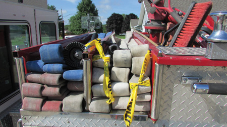 This hose deployment method will work with a standard flat load without strategically placed loops. The firefighter must locate the fold that corresponds to the first coupling (50 feet) from the nozzle. The nozzle loop is the higher marked fold. For this photo, the corresponding folds were marked with scene tape and chalk.