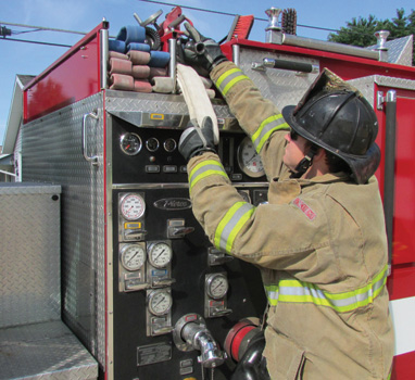 (6) For two-firefighter deployment, the nozzle firefighter grasps only the nozzle and nozzle firefighter loop. (Photo by Josh Graham.)