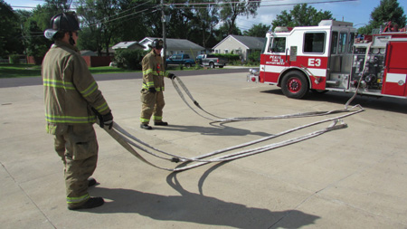 (7) As the nozzle firefighter stretches the attack hoseline, the backup firefighter has pulled the backup firefighter loop and is stretching the remaining hose. The