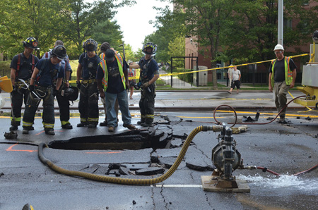 (3). A broken water main has left a water-filled sinkhole that public works personnel are pumping out. At night, flowing water would hide the hole. A firefighter could easily step into the hole if he was careless enough to enter the water without probing ahead with a tool as he walked. (Photo by Lloyd Mitchell.)