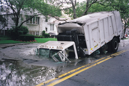 The truck's driver drove into what he thought was a puddle, but it was actually a sinkhole created by a burst underground water main. The undermined roadway collapsed under the truck's weight.
