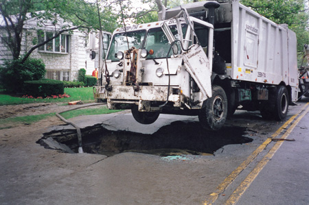 To remove the truck, a crane lifted the front of the truck while a tow truck stabilized the rear to keep it from being pulled into the hole by the crane. The hoseline maintains the water level above the shut-off water main to prevent contaminants on the water's surface from back-flowing into the water supply.