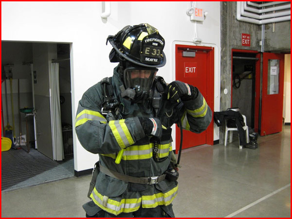 A firefighter wearing his turnout gear accessing his radio.