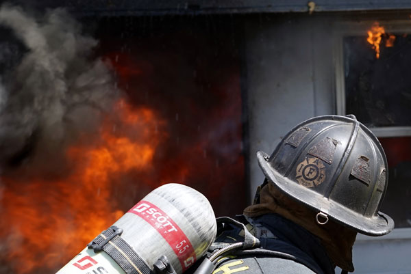 A firefighter confronts a heavy volume of fire.