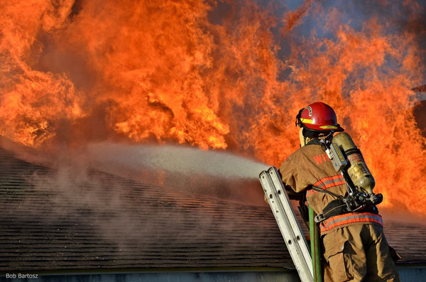 Flames erupt from the roof oa North Carolina home as a firefighter in full gear uses a hoseline to apply water while at the top of a ladder.