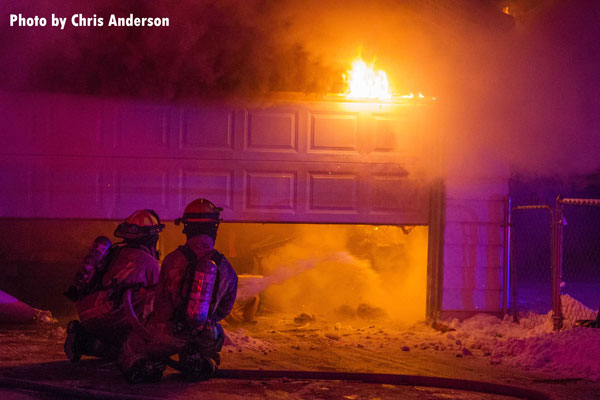 Firefighters apply water to a burning garage in Machesney Park, Illinois.