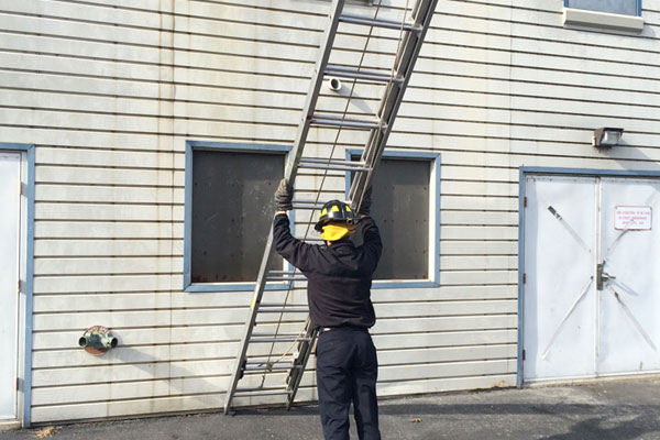 A firefighter raises a ladder during a training drill.