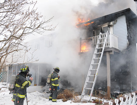 (2) A view of the rear of the building. You can see how the fire started on the first floor, exposed the outside of the building, and traveled to the soffits. This allowed fire to get into the attic space.