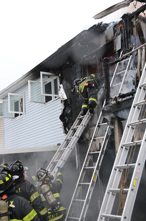 (7) The member was allowed room on the ladder to spin and come around to a feet-first descent. Members at the base of the ladder braced it for safety.