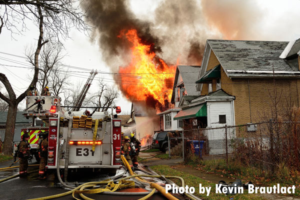 Buffalo (NY) firefighters on a rig as fire blows out of a home.