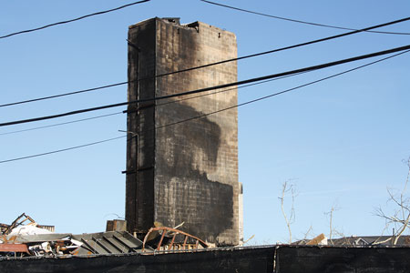 """Where is the wood? All that was left of the Edgewater (NJ) pedestal LW structure (660 ft. × 255 ft.) were the masonry elevator hoistway, two vertical stair towers, and the under-the-garage platform from which the residents were able to drive away in their vehicles.<i> (Photo by Ron Jeffers.)</i>""""></td> </tr> <tr> <td align="""