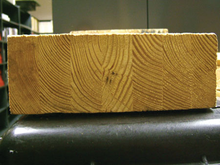 """(3) """"Fast-growth"""" wood. This is a lam-beam, which is a series of smaller engineered beams glued together. Note the width of the rings. There is lot of moisture in this member. It will dry out and warp inside the structure."""