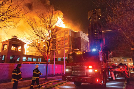 """(5) Pedestal buildings such as this structure incorporate base-level """"pedestals"""" on which the wood-frame dwelling units are built. The lit windows pictured are illuminating the parking level for residents, which was the only portion of the structure left standing after this massive fire."""