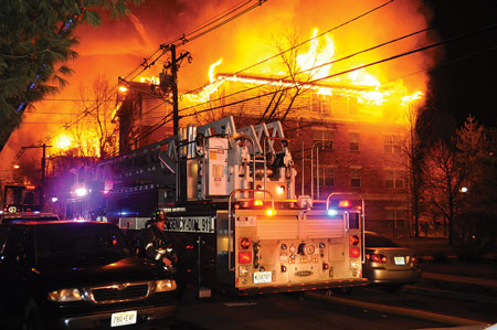 """(6) This photo, taken near the corner of Building A, shows the difficulty firefighters had accessing the fire building even from the public street because of the congestion from cars parked on both sides of the narrow street. <i>(Photos 6-8 by Keith Addie.)</i>  """"></td> </tr> <tr> <td align="""