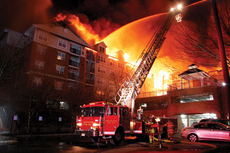 (9) A tower ladder applies water to Building C. Note the lack of access to the rear portion of the building. (Photo by Chris Tompkins.)