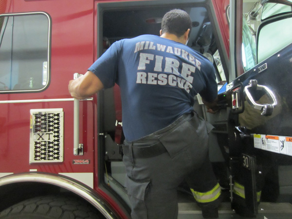 A firefighter performs a hip hike movement to board the apparatus.