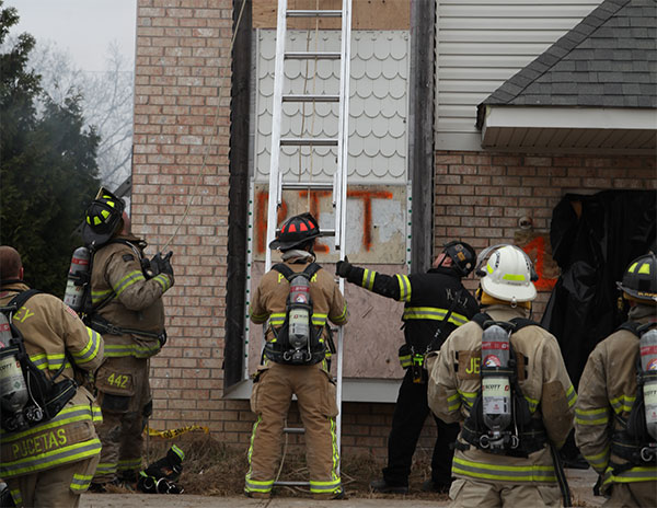 A firefighter holds a ladder on the training ground.
